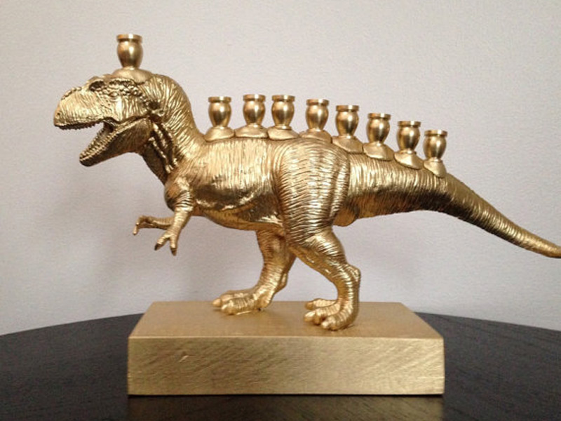 "A ""Menorasaurus"" -- a Hannukiah made by gluing candle holders to a plastic T-Rex, mounting it on a wooden base, and spray painting the whole thing gold"